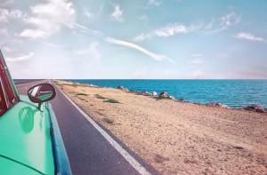 car driving next to ocean